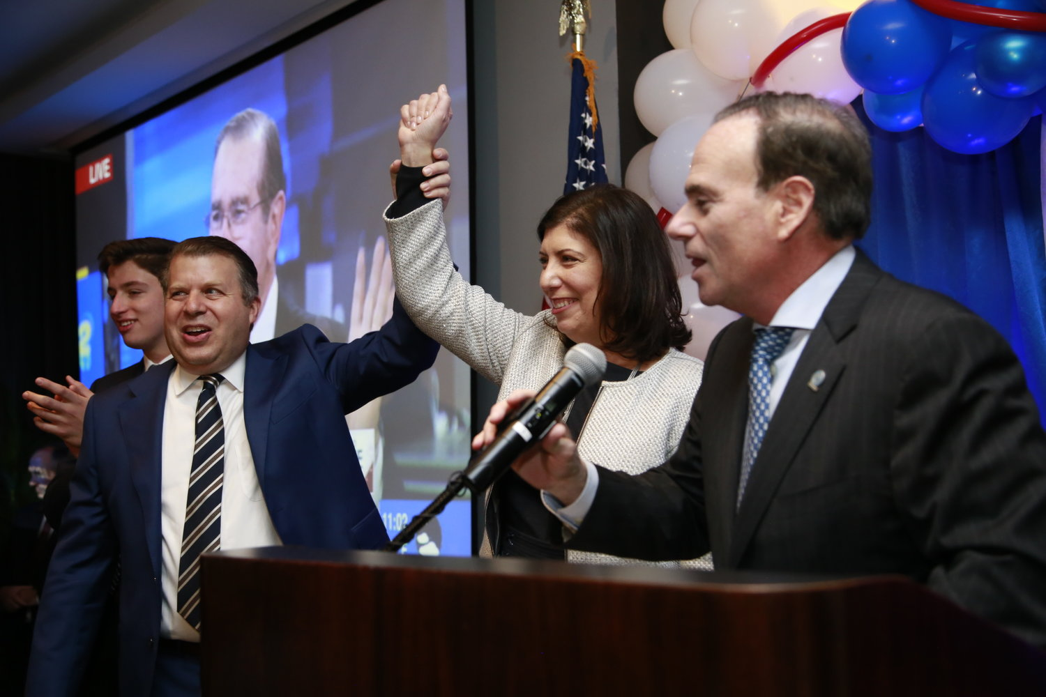 Nassau County District Attorney Madeline Singas declared victory early. She was joined here by her husband, Theo Apostolou, left, and Nassau Democratic Party Chairman Jay Jacobs.