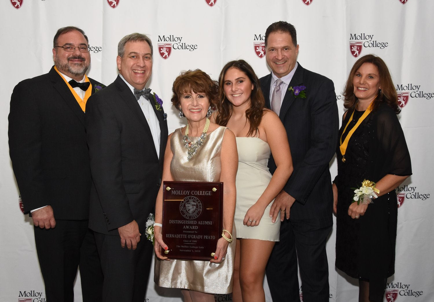 Bernadette O'Grady Prato, Class of 1980, holds her Distinguished Alumni Award and is pictured with, from left, event co-chair Salvatore Ciampo, Molloy College President Dr. Drew Bogner, her daughter, Dominique Prato, husband Gregory Prato and event co-chair Laura Farahani.