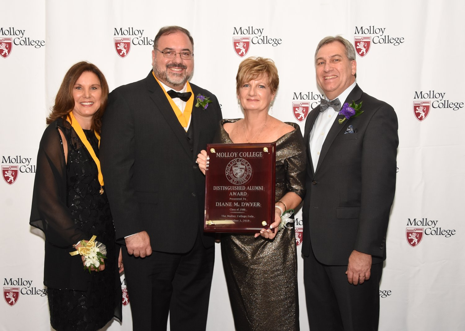 Distinguished Alumni Award winner Diane M. Dwyer with, from left, event co-chairs Laura Farahani and Salvatore Ciampo and Dr. Drew Bogner, president of Molloy College.
