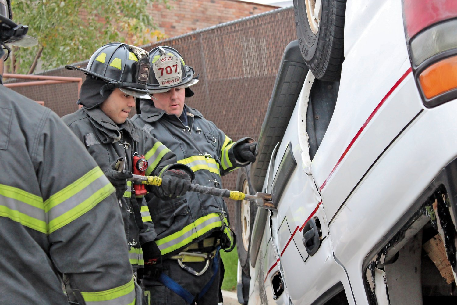 Firefighters Sebastian Pimentel and Patrick McNeill pried open the door of the overturned car.