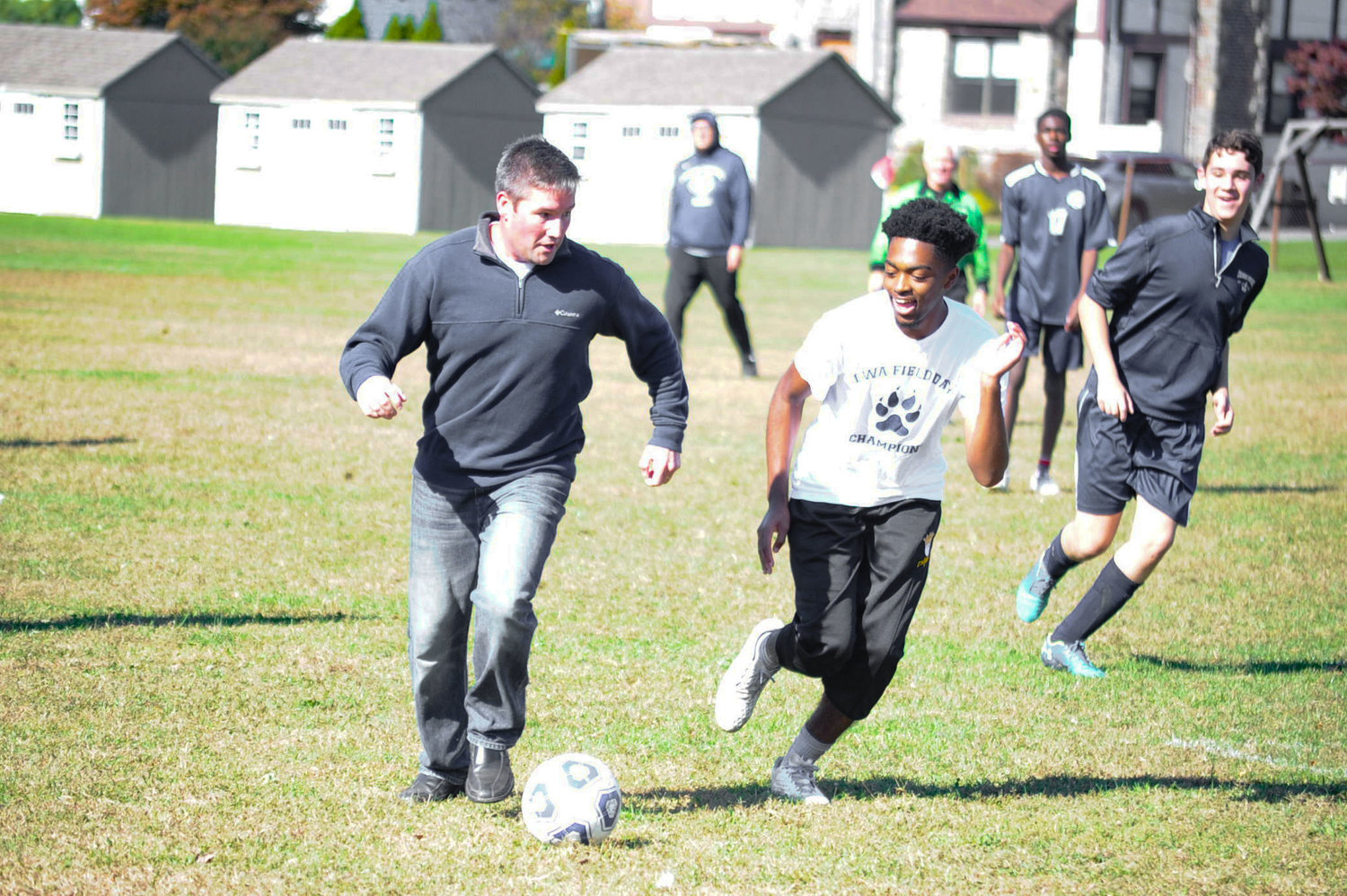 Lawrence Woodmere Academy's Director of Admissions Luke Davis looked to dribble past Daniel Carrion in the teachers vs. students game at LWA's Homecoming on Oct. 19.