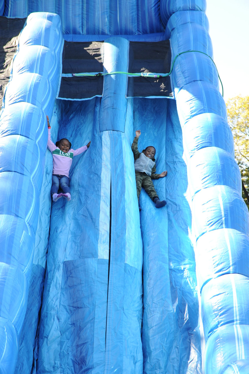 The big slide's height and decline distance did not deter Briyel Merceron, left, and Lyn Alexis from going down.