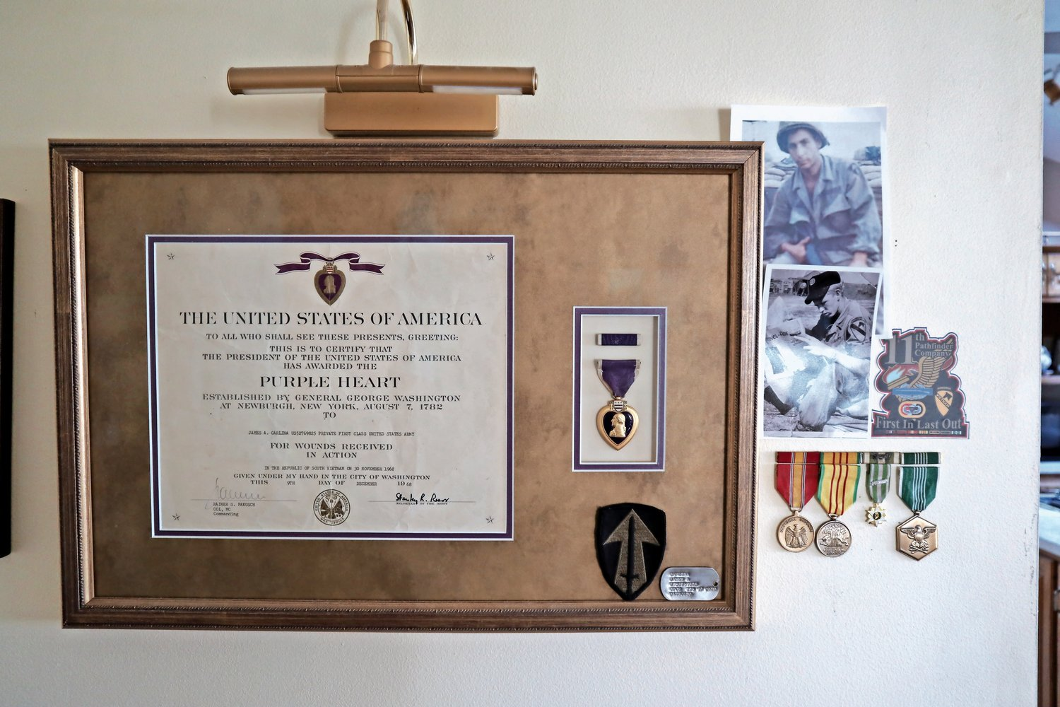 Jim Carlina's Purple Heart is framed and hangs on a wall in his home. His photo, above right, is now accompanied by one of Curtis Davis, the man who helped save Carlina's life more than 50 years ago. The two reconnected earlier this year.