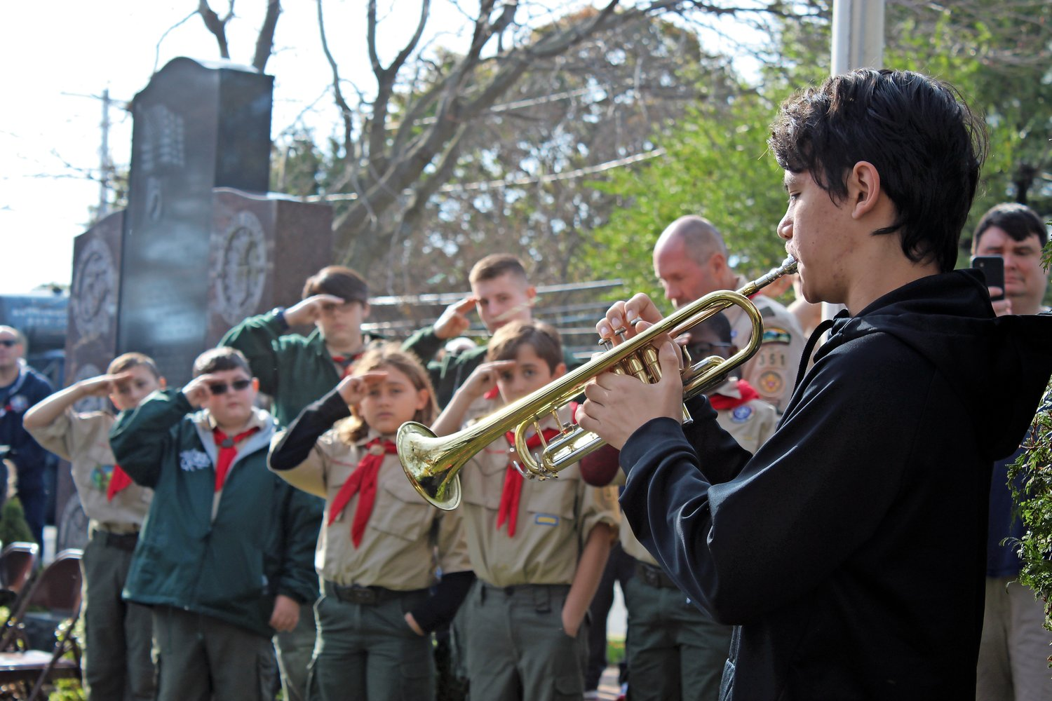 At American Legion Post 1282's annual Veterans Day ceremony on Monday at Veterans Memorial Park in Merrick, Calhoun High School freshman Hayden Okonowitz played taps as members of Boy Scout Troop 351 saluted.