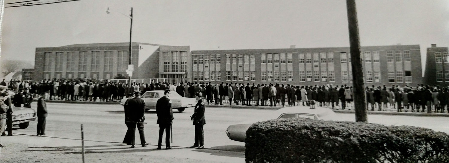 Residents and protesters crowded Ocean Avenue, in front of Malverne High School, circa 1963, over plans to integrate Malverne Public Schools.