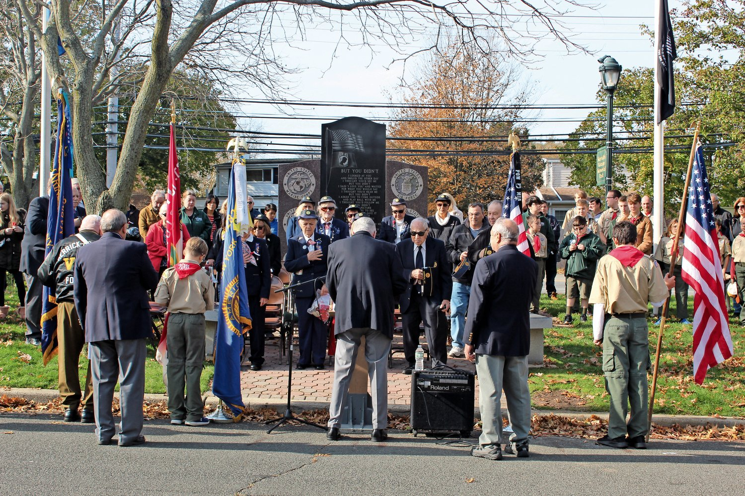 A humble crowd gathered in front of Merrick's veterans' memorial, left, in observance of Veterans Day.