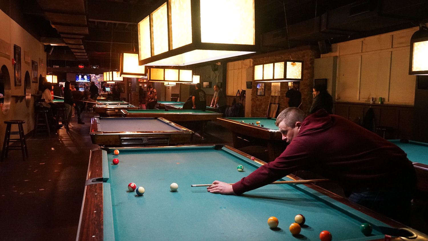 A patron shot a game of pool on the last Saturday before Guys and Dolls was set to close.