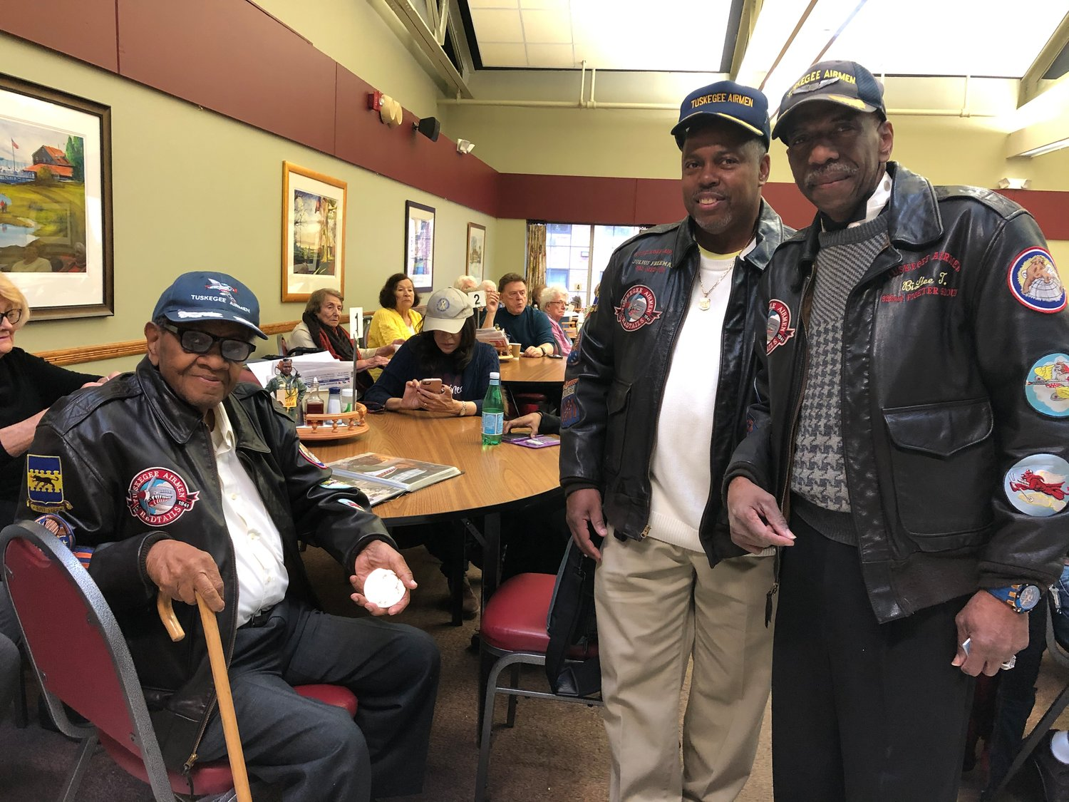 Tuskegee Airmen historians William Thomas Jr., near right, and Joe Martin with Tuskegee Airman William Johnson at the Glen Cove Senior Center.