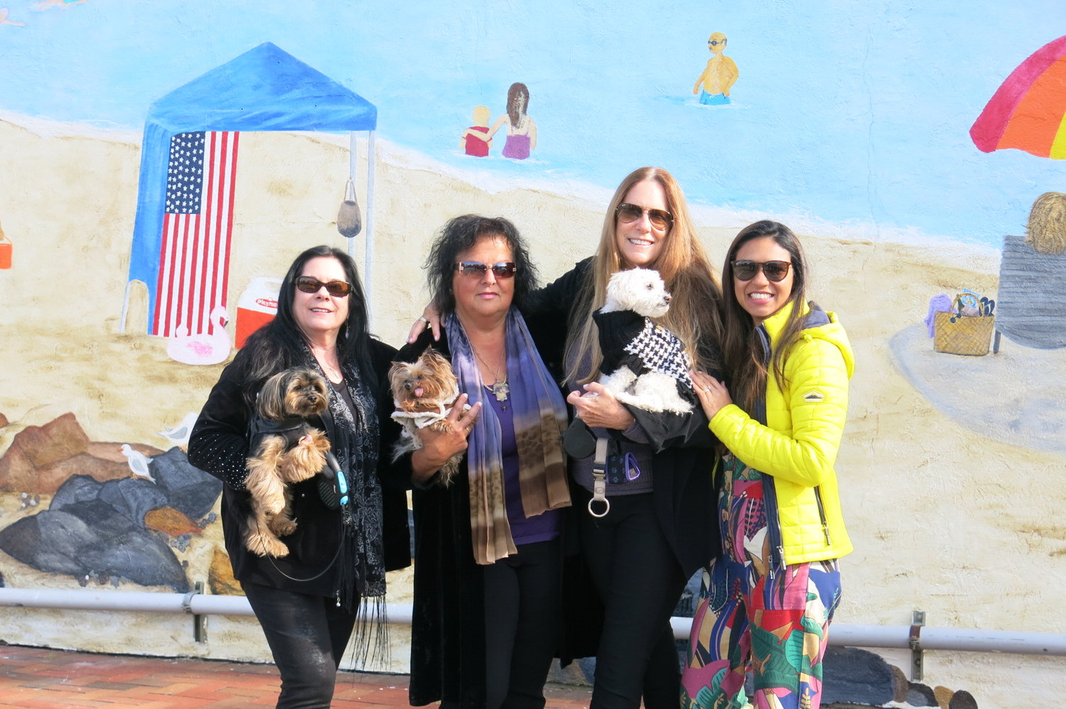 Several artists worked on the Bayville Centennial Mural to commemorate the village's 100th birthday, including, from left, Deborah Webbe, Anna Laruccia, Barbara Wendt-Keller and Pricila Modesto. Laruccia created the view of a typical beach day in Bayville.