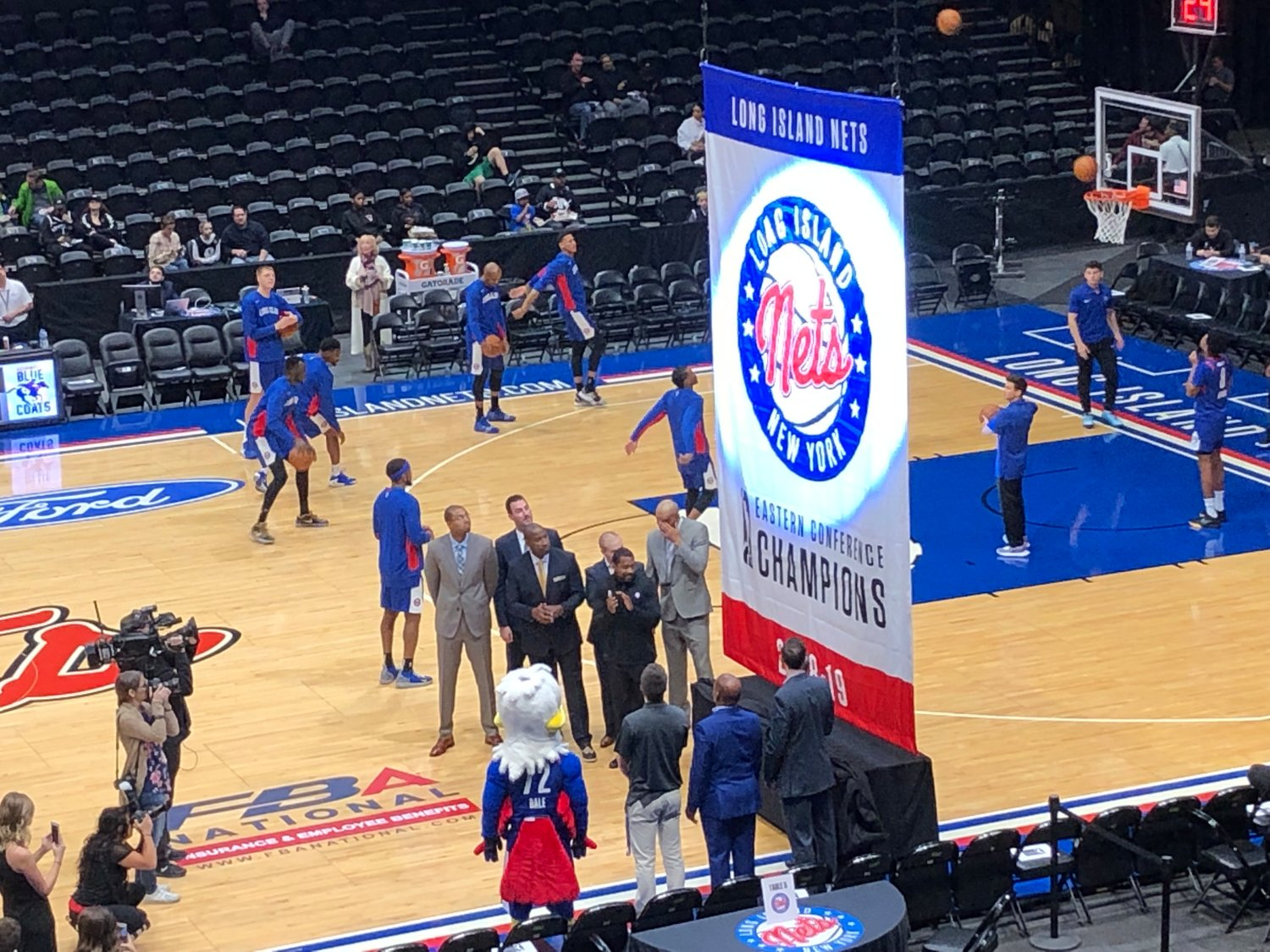 Long Island Nets coaches and management help raise the club's 2018-19 NBA G League Eastern Conference Championship banner Friday night before the team's home game against the Delaware Blue Coats at NYCB Live's Nassau Coliseum.
