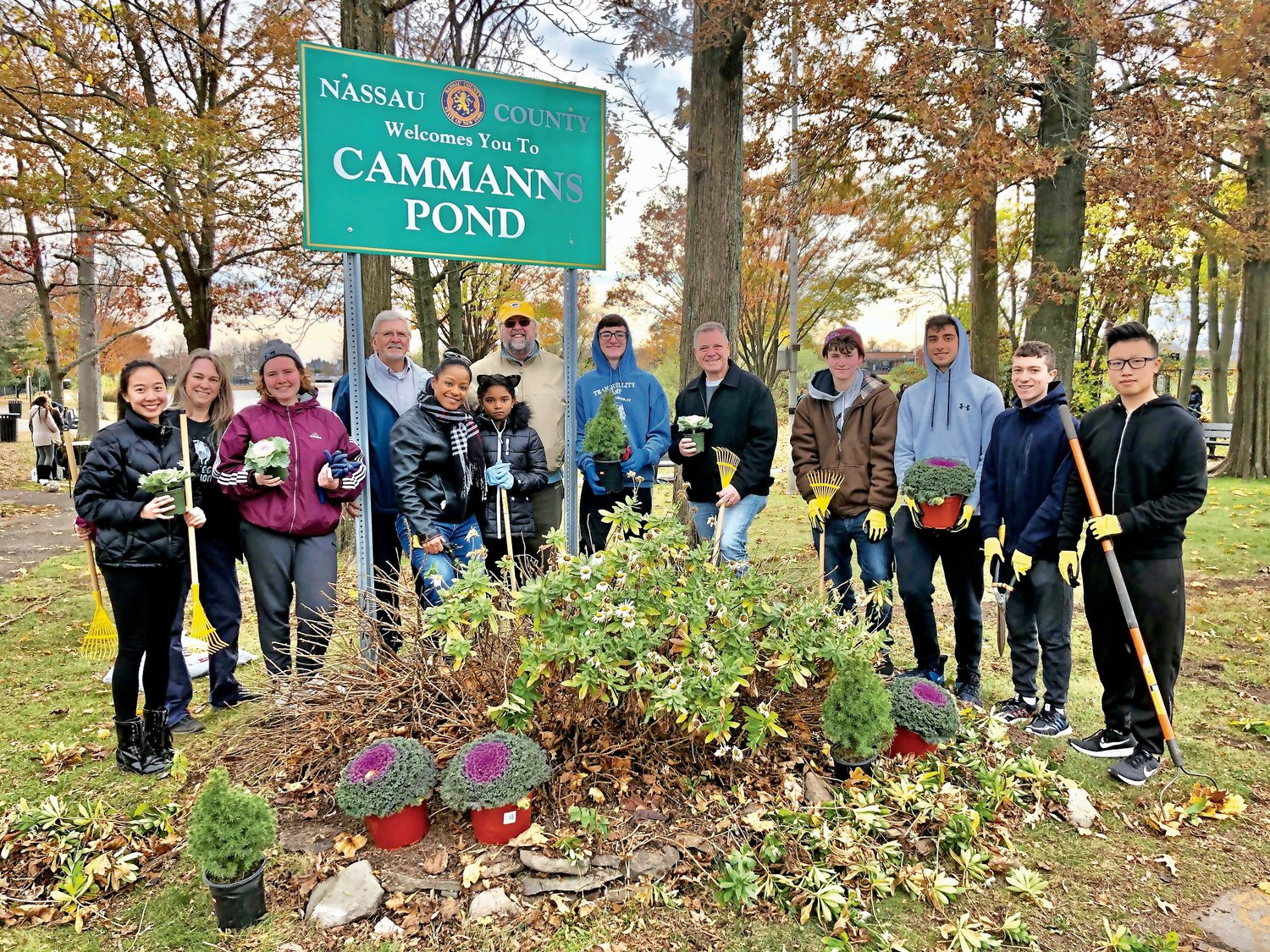 Fresh plants were placed around Cammanns Pond's welcoming sign. Nassau County Legislator Steve Rhoads, fifth from right, joined in the effort.