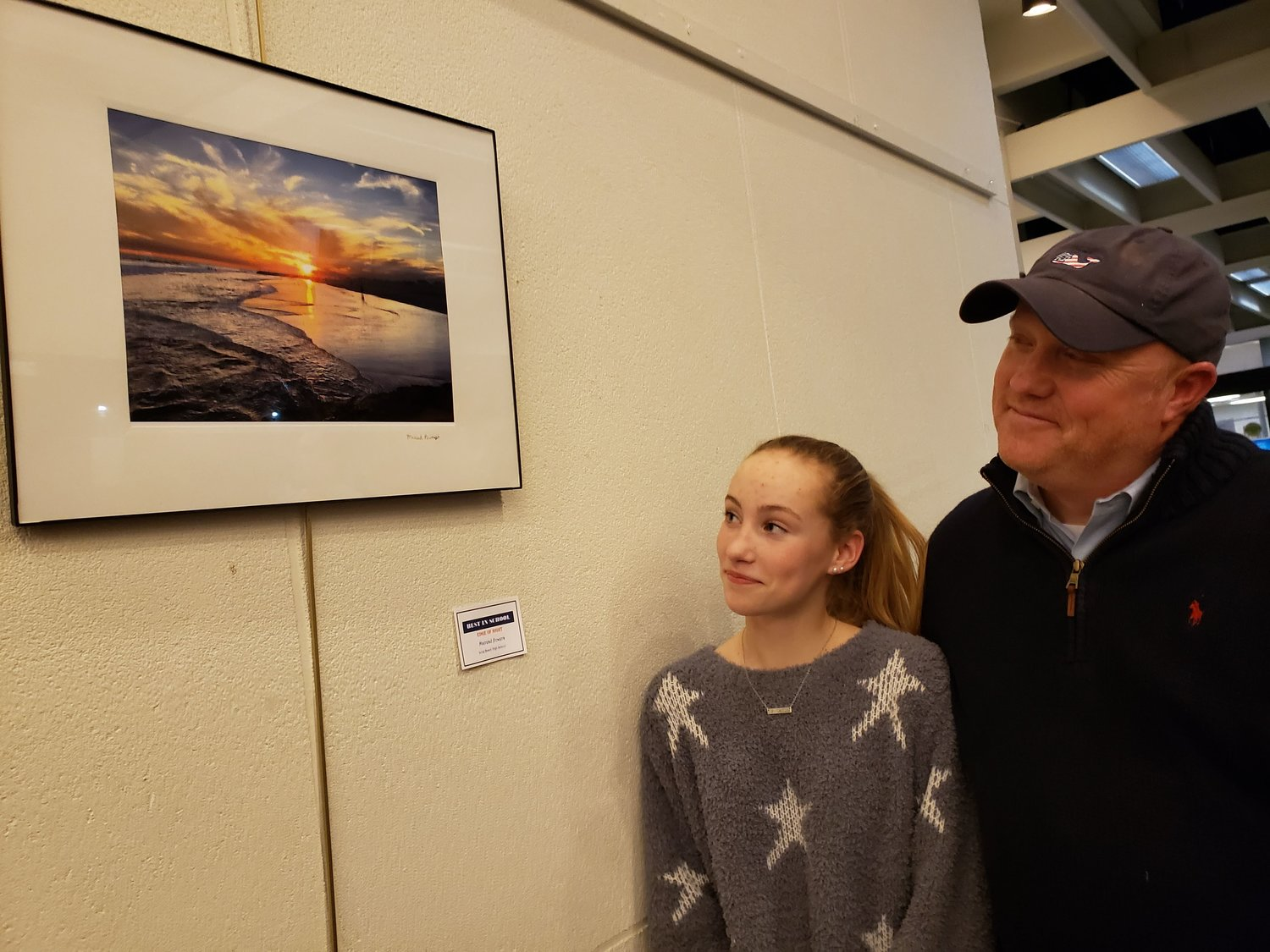 Long Beach High School junior Mairead Powers, 16, below, showed her father, Raymond Powers, her Best in Show photograph of a sunset.