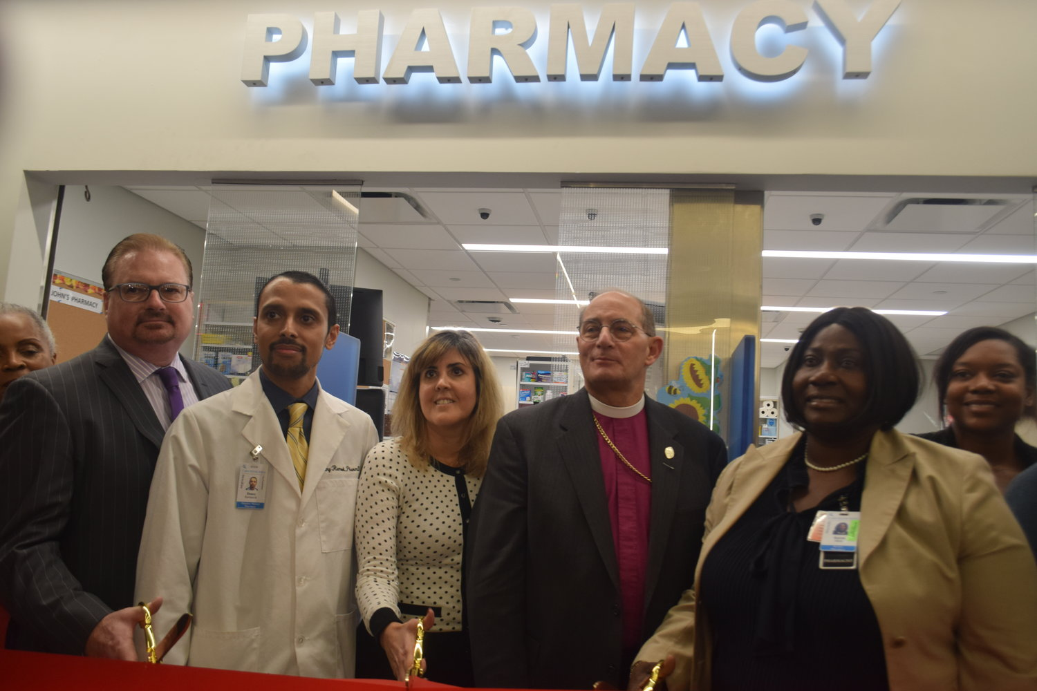 Gerard Walsh, CEO of St. John's Episcopal Hospital, far left, pharmacy Manager Donny Ramsook, Maxor operations Vice President Maria Booker, Bishop Lawrence Provenzano and pharmacy Director Karen Muir cut the ribbon.