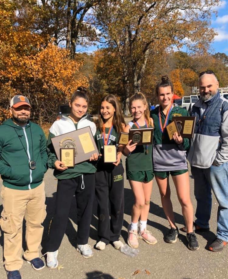 The Lynbrook girls' cross-country team captured its first Nassau County Class III title in program history on Nov. 2. Coach Pete Toscano, far left, Caitlin Buchala, Mimi Berkowitz, Kaelyn O'Brien, Liz Murphy and coach Joe Beyrer celebrated the victory.