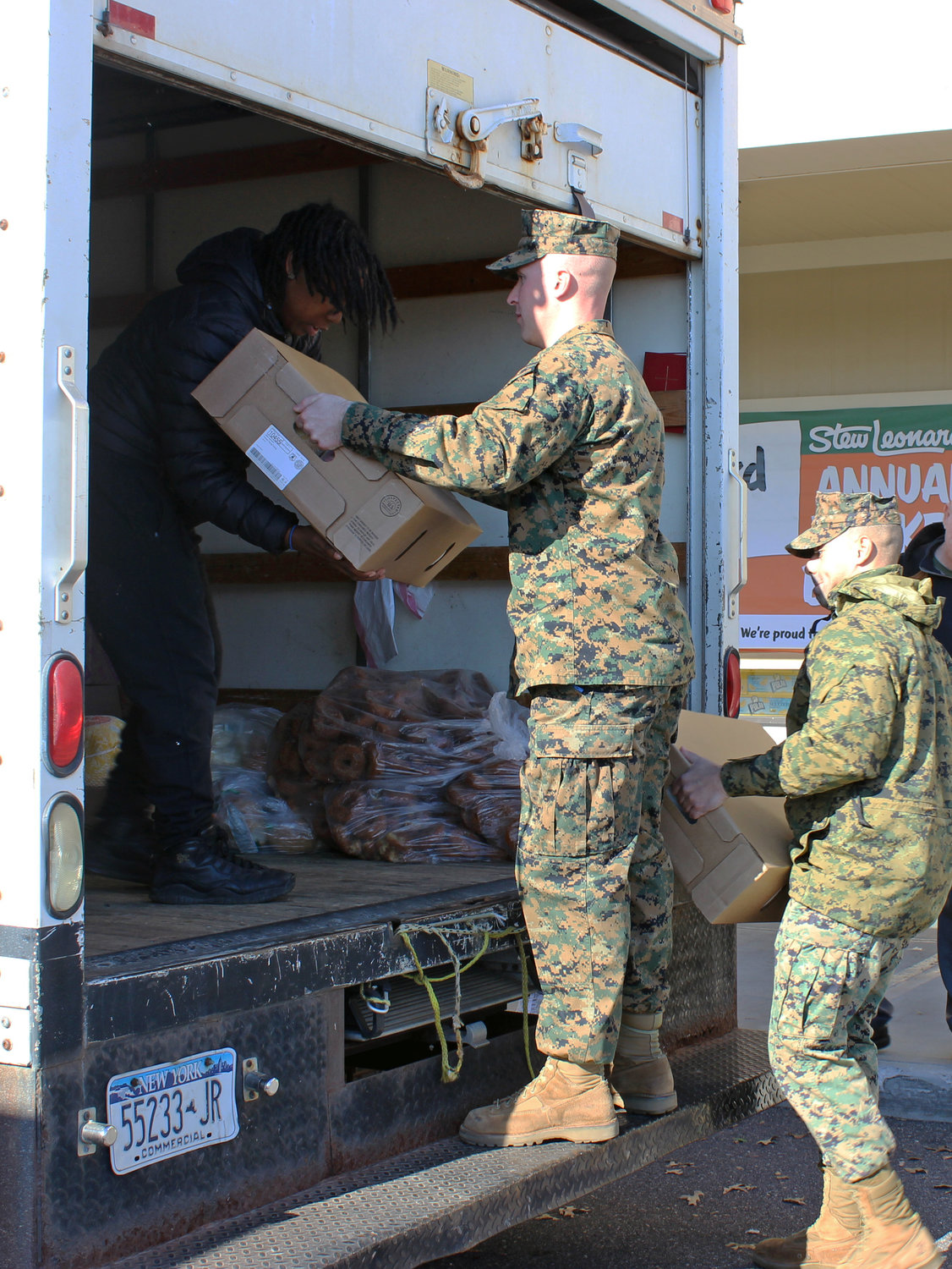 Gunnery Sgt. John Sardine, above center, and Sgt. Jake Stanuch, both of the Marine Corps' 2nd Battalion, 25th Marines unit in Garden City, loaded turkeys for delivery to the Mary Brennan Interfaith Nutrition Network in Hempstead.