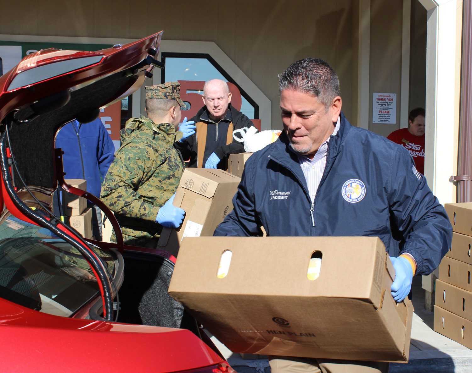 "James McDermott, president of the Nassau County Police Benevolent Association, loaded turkeys into cars to be delivered to local charities as part of Stew Leonard's ""Turkey Brigade,"" in which it donates Thanksgiving turkeys to local charities."