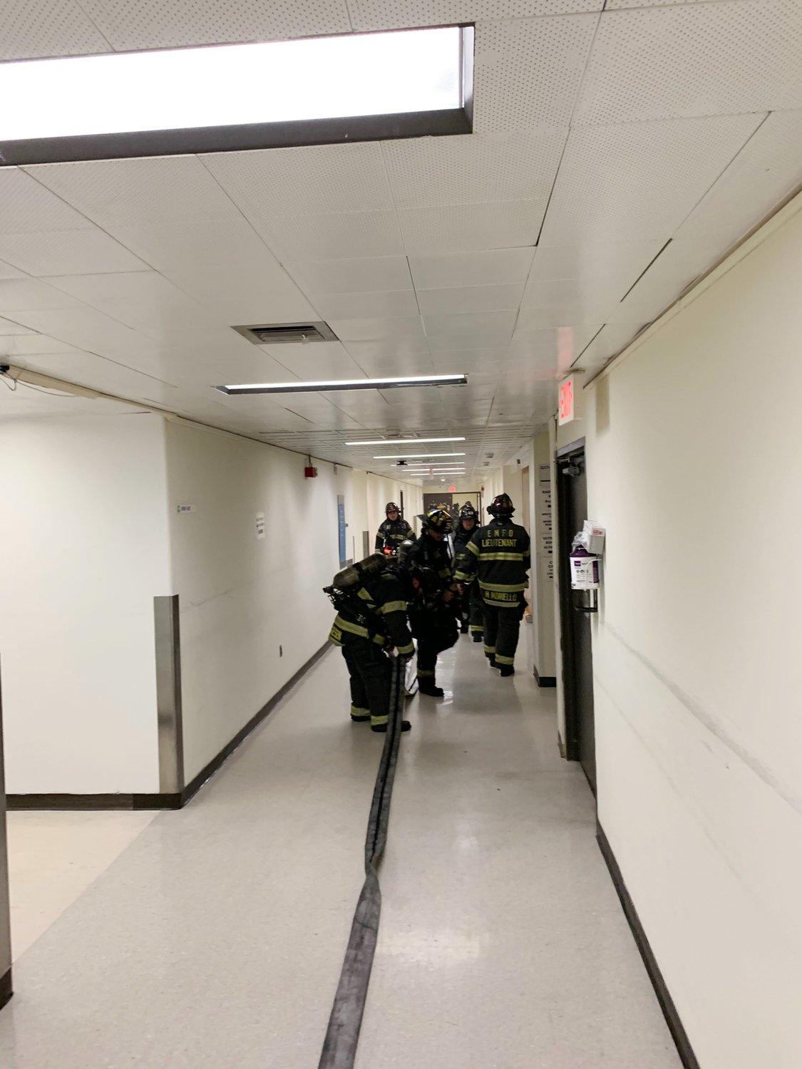 "With crews ""taking up,"" volunteers began picking up the attack hose stretched in a second-floor hallway."