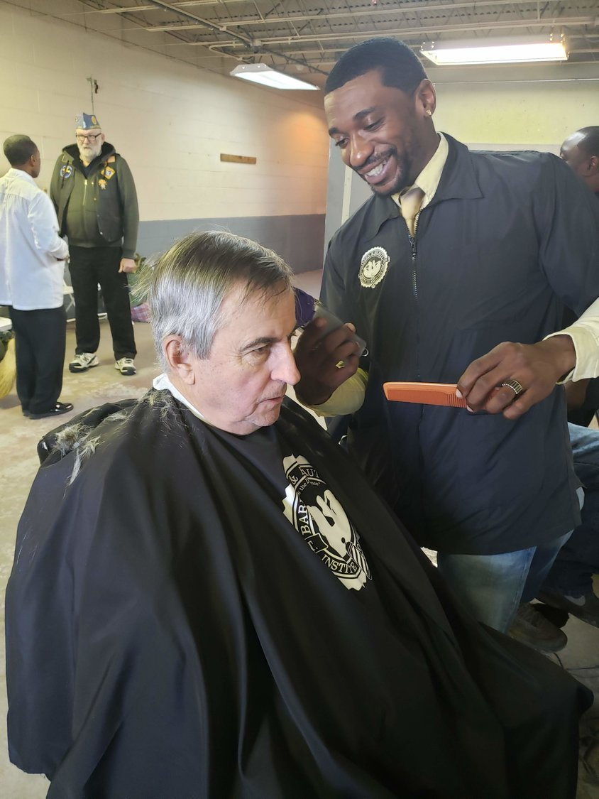 Army veteran and barber student from Barber and Beauty Institiute of New York in Hempstead, Raeisi Daniels cuts Marine, Tom Holloran's hair during the winter Veteran Stand Down at the Freeport Armory in Freeport on Nov. 26.