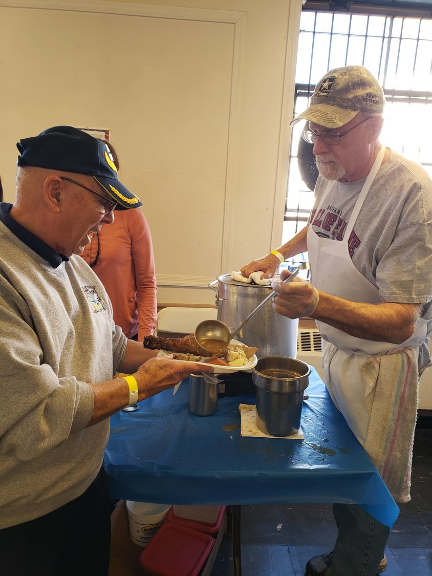 Navy veteran Frank Gallo from Bellmore participated in the meal served for veterans by one of the volunteers, Matthew Bonini an Army veteran from Baldwin.