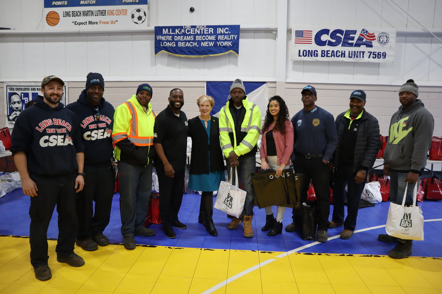 James Hodge, fourth from left, and state Labor Commissioner Roberta Reardon, fifth from left, were joined by city employees who volunteered at the turkey giveaway on Nov. 26.