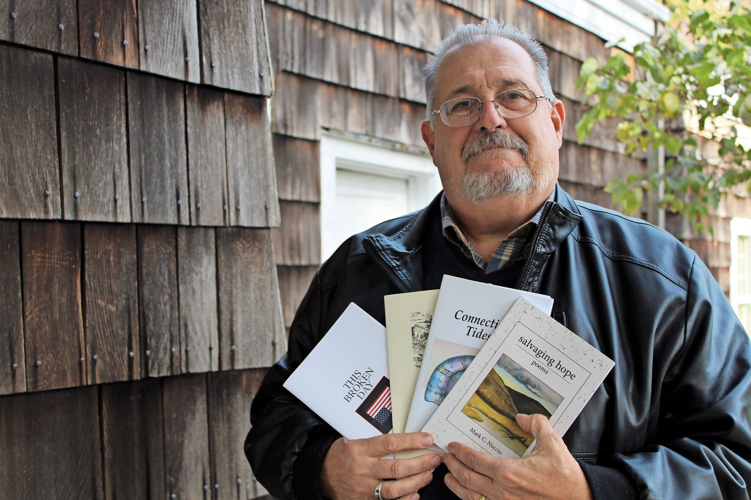 Bellmore artist and poet Mark Nuccio with a collection of his published chapbooks — small books of poetry — at the Walt Whitman Birthplace in Huntington, where he is treasurer of the board of trustees.