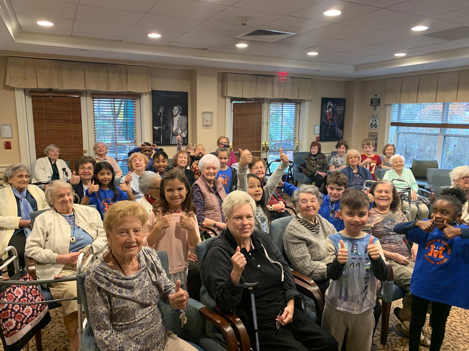 Students and senior citizens gave a thumbs up at Atria's Assisted Living.