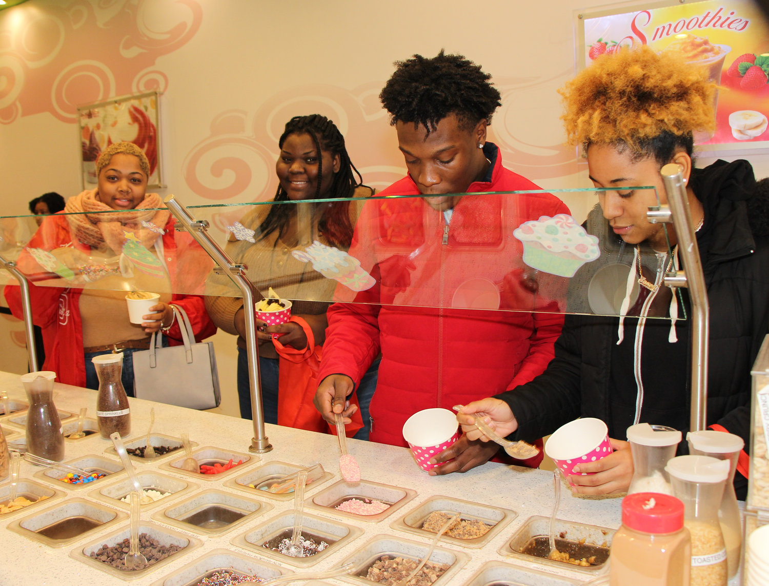 Dominique and Saniya Powell, left, Nigel Jarvis and Josey Cruz chose toppings for their frozen yogurt treats at Swirl Bliss.