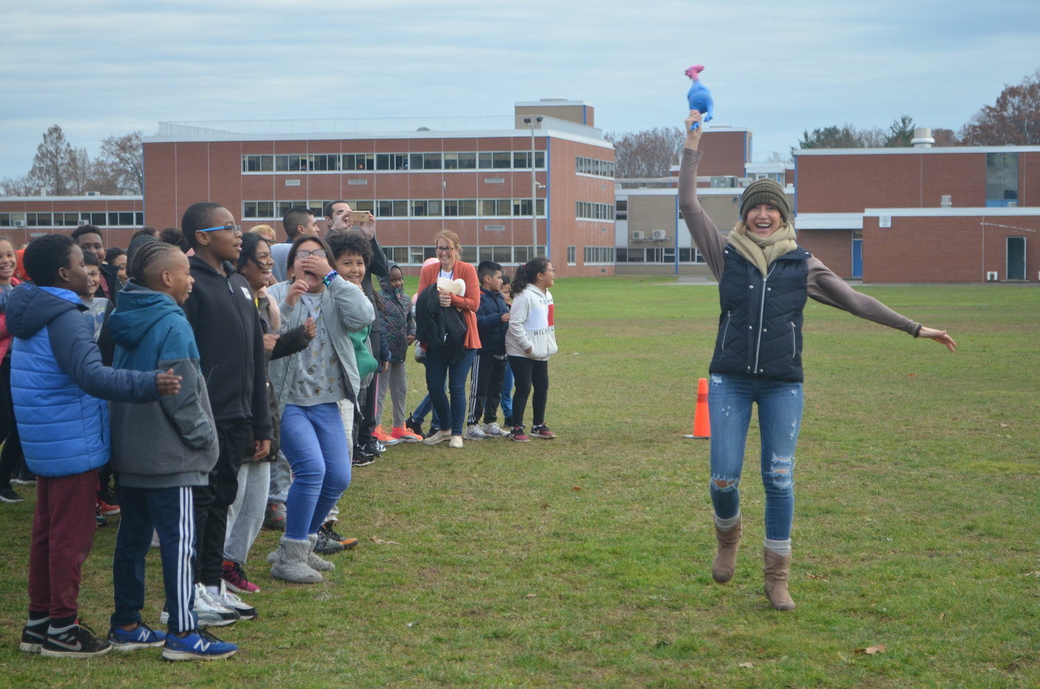 Michelle-Dionisio, a fourth-grade teacher at Brookside Elementary School, skipped down the field with a rubber chicken on Nov. 27 at the school's first Turkey Trot to benefit local food pantries for Thanksgiving.