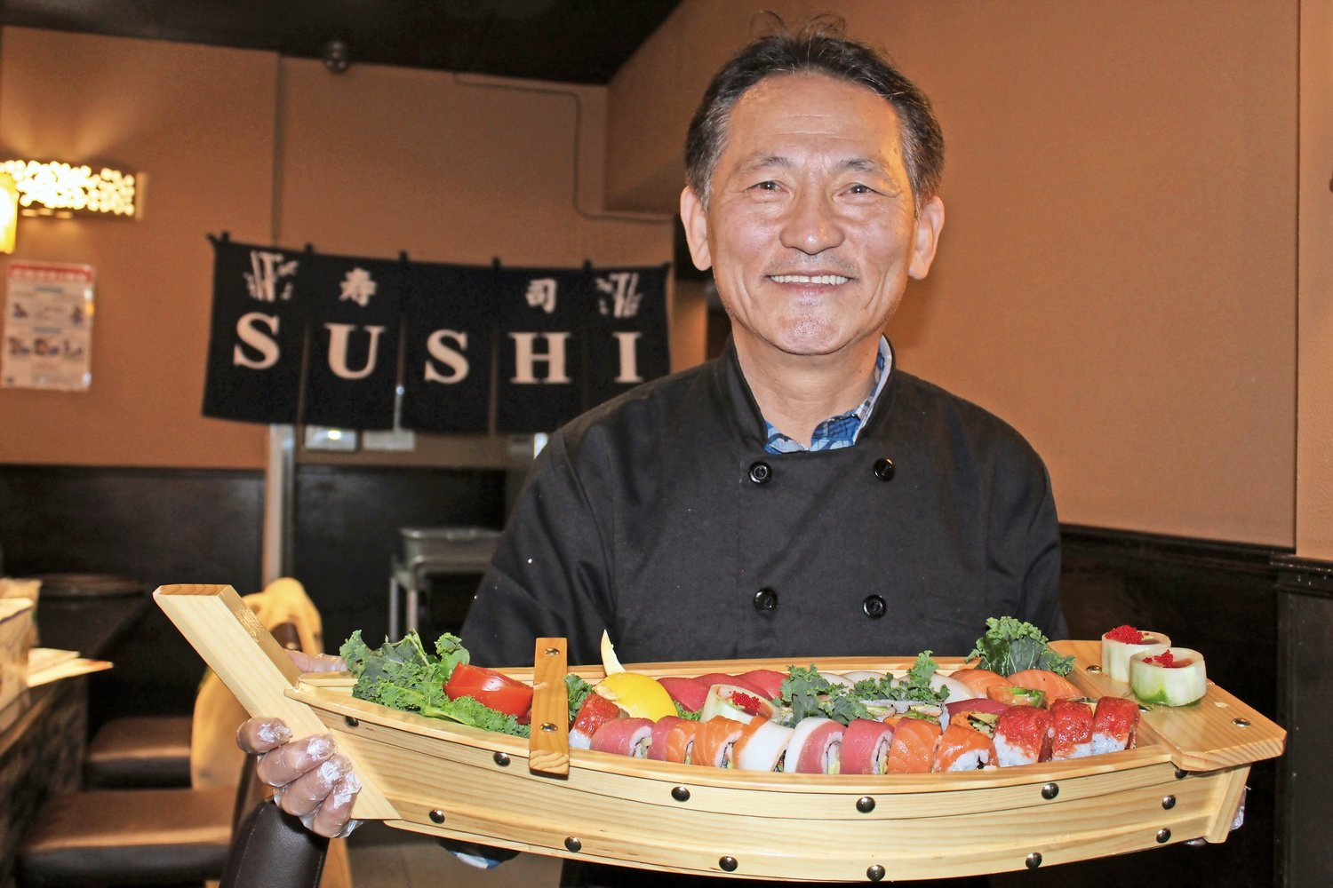 David Sim, the new chef and owner of Fuji Seoul in Merrick, proudly displayed the restaurant's mizu sushi boat.