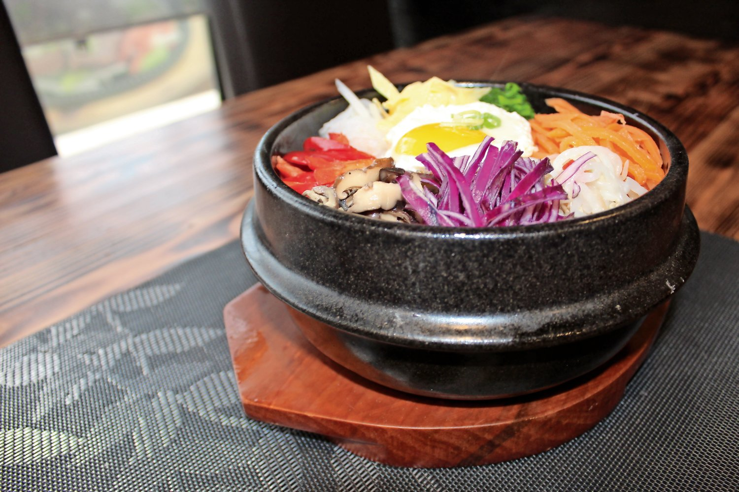 The dolsot-bibimbap is a vibrant Korean rice dish topped with a colorful array of vegetables and served in a stone pot.