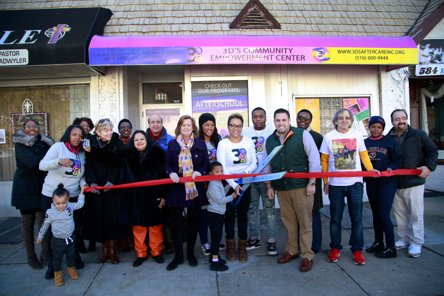 Williams, center, with family and community members, cut the ribbon on 3D's Community Empowerment Center last winter.