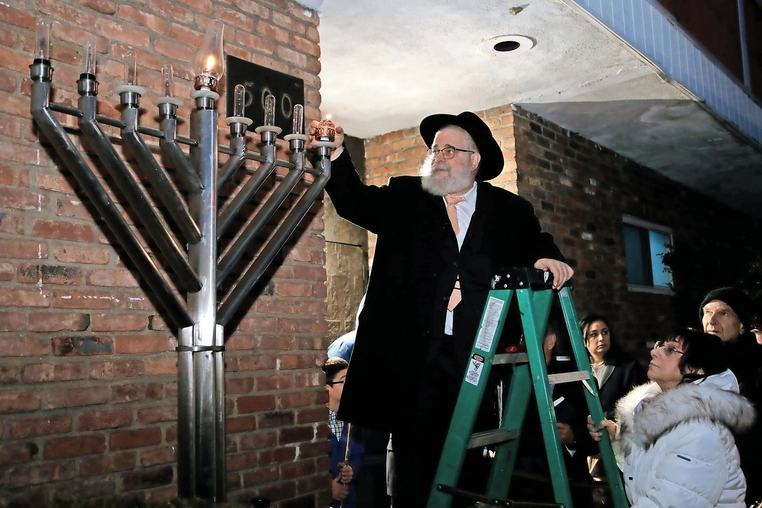 Rabbi Chaim Blachman, of the Elmont Jewish Center, lit the first candle of the menorah on Dec. 22.
