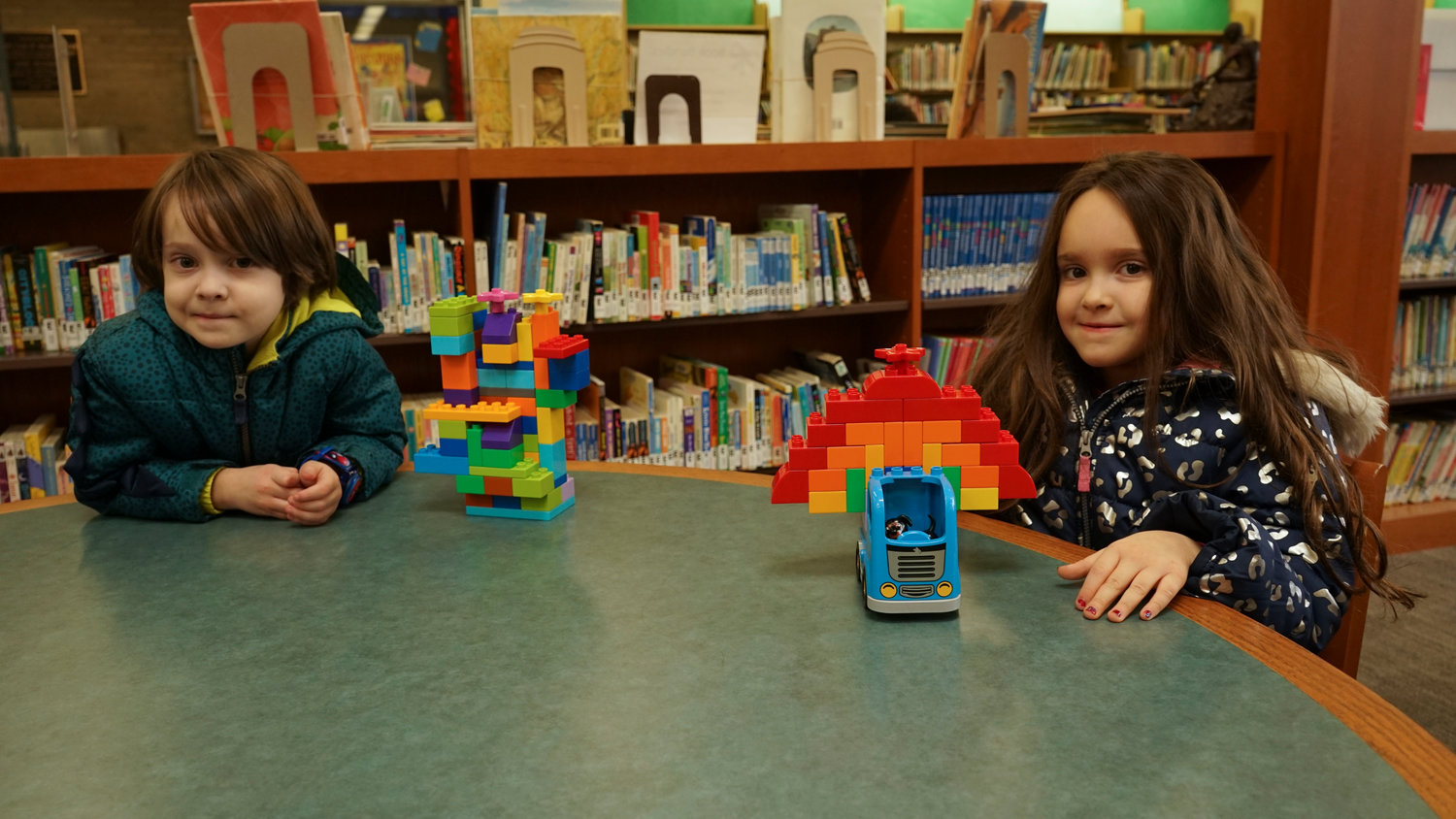 Siblings Adrian, 4, and Annabelle, 6, with their displays: a haunted house and a Rainbow Bulldozer Truck.