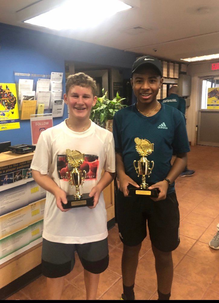 Schorr, left, and his partner, Zavier Augustin of Malverne, with their doubles trophies.