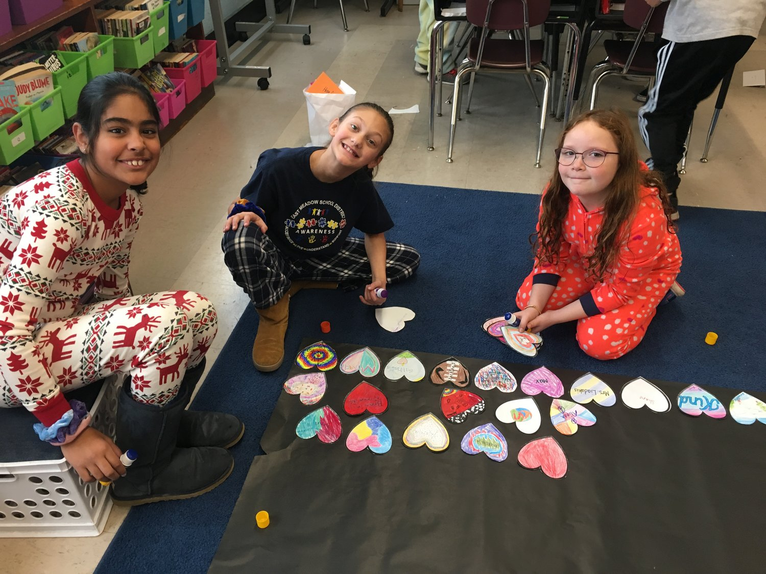 "Fifth-grade students Zaina Ahmad, Emilie Sarrantonio and Madeline Piper, of Bowling Green Elementary School, personalized tags to attach to the gifts they had purchased through a ""Hope for the Holidays"" fundraising project."