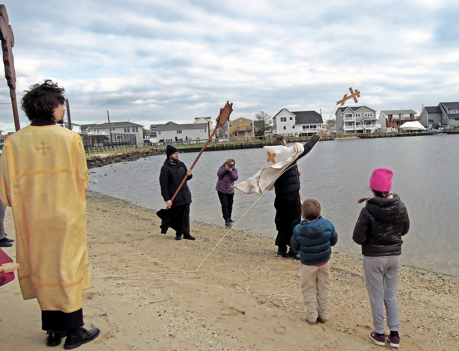 V.Rev. Martin Kraus threw the traditional wooden cross into the bay three times.