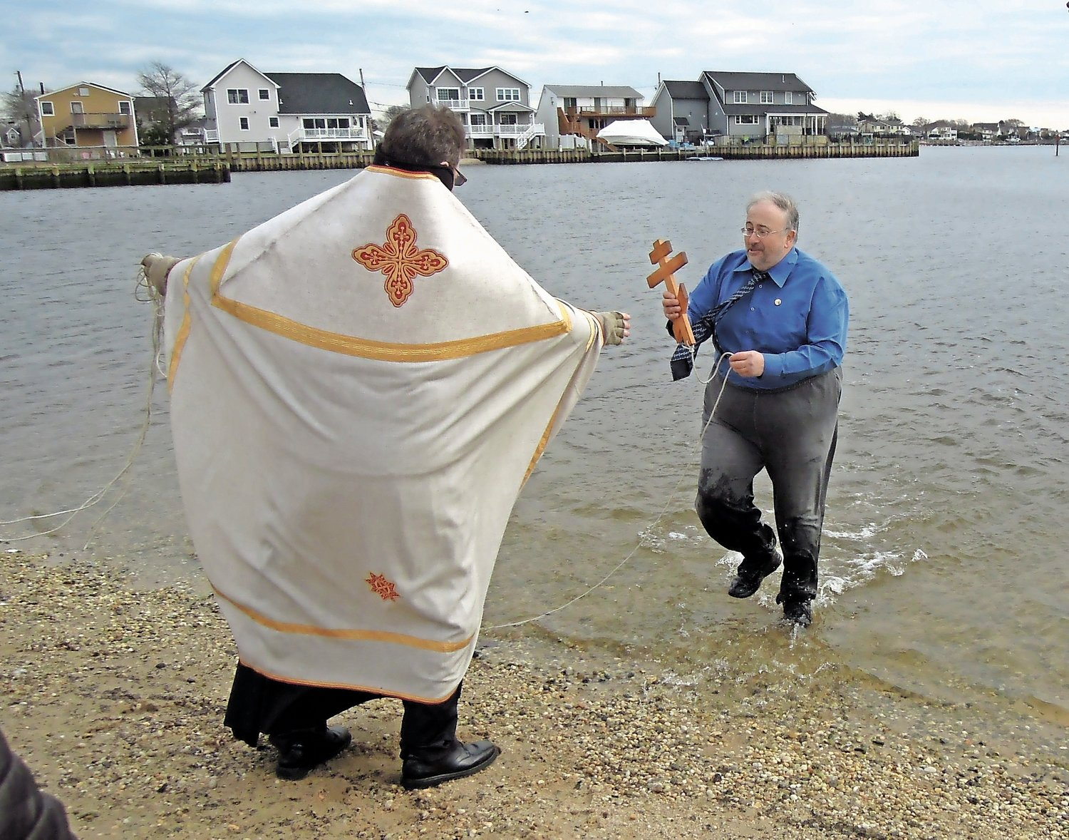 On the third time, a parishioner dashed into the water to retrieve the cross.
