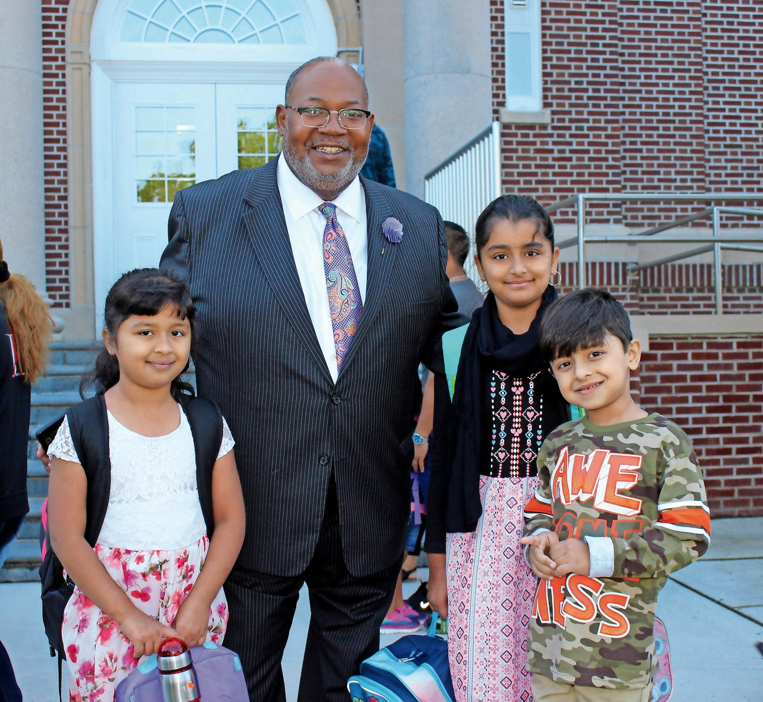 Al Harper greeted, from left, Sara and Fiza Shahdat and Tabish Bhatti on the first day of school in 2017.
