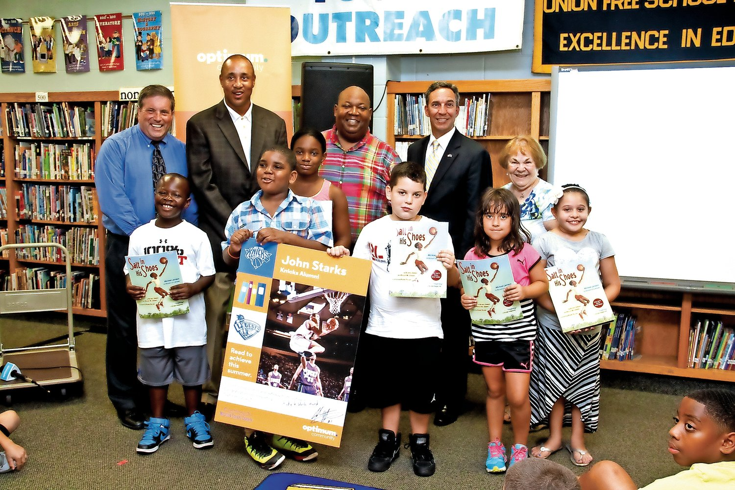 Al Harper, standing second from right, joined representatives of the New York Knicks and Cablevision, students, school administrators and local officials at the ninth annual Knicks Read to Achieve event at Covert Avenue School in the summer of 2015.