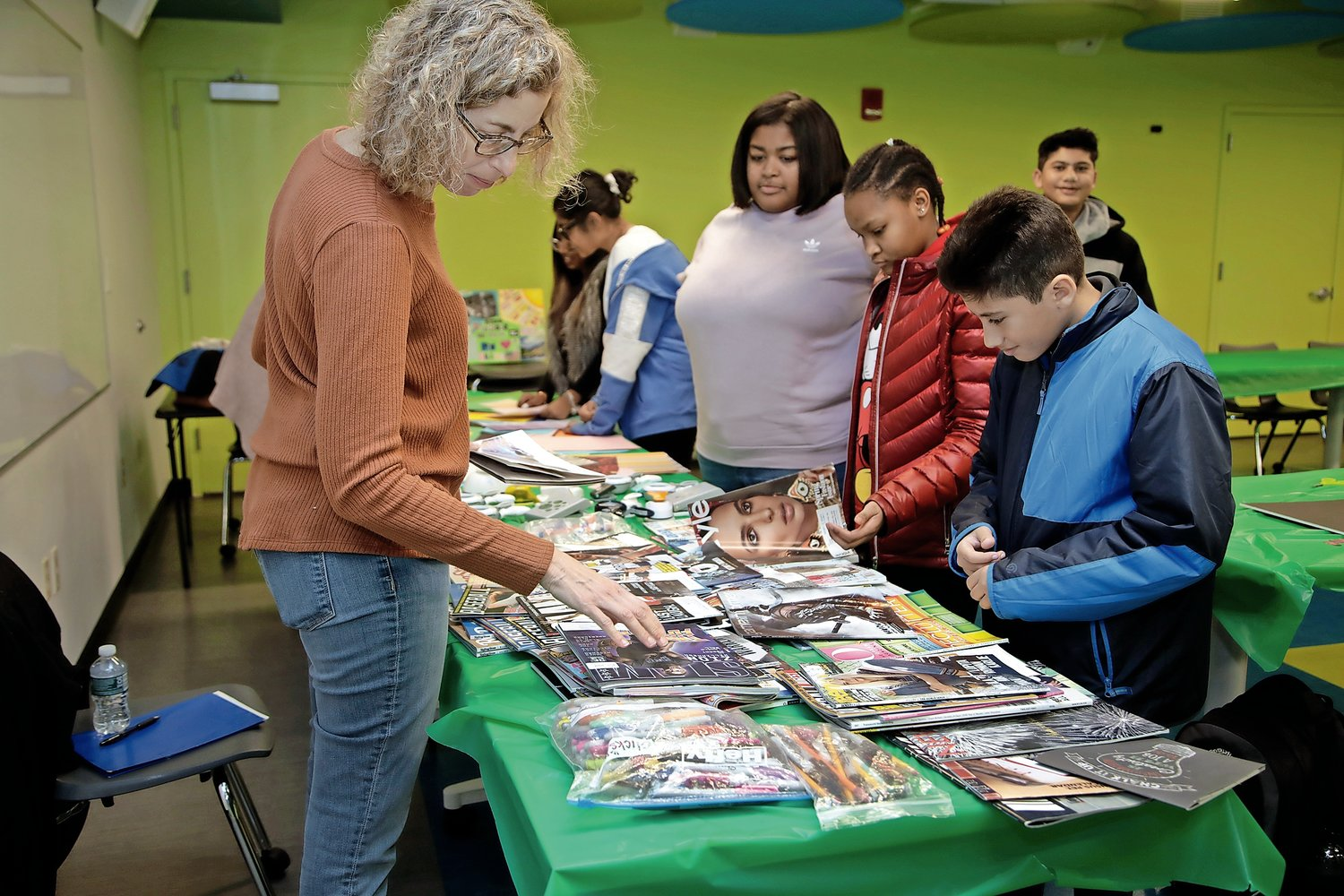 Leslie Sattler, of Green Earth Craft, browsed through magazines for Joe Davis, Erin Simon and Ismael Sohail at the Elmont Memorial Library on Jan. 7.