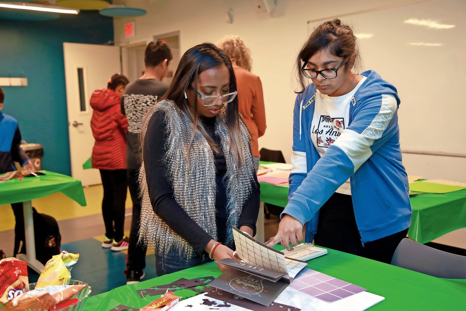 Elmont Memorial High School senior Natalia Bisnauth, left, and freshman Emily Sukhnandan looked for inspirational sayings from a calendar to use on vision boards that they made at the Elmont Memorial Library.