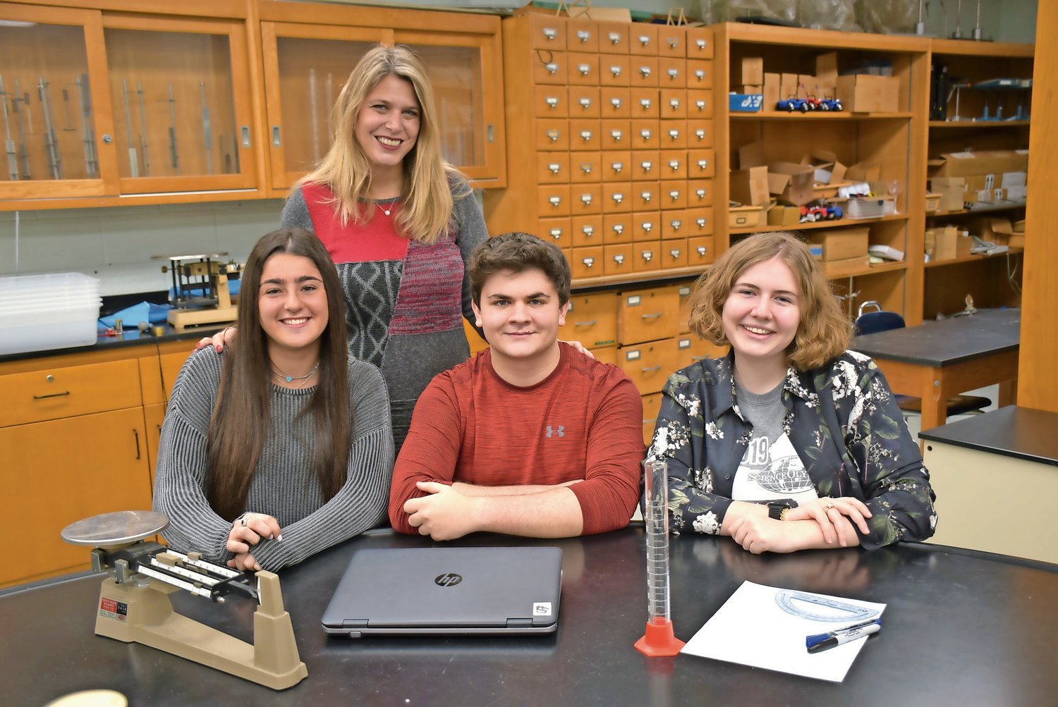 John F. Kennedy Advanced Science Research teacher Barbi Frank, standing, helped seniors Kenar Gelman, left, Andrew Brinton and Katherine St. George on their projects for the Regeneron Science Talent Search competition.