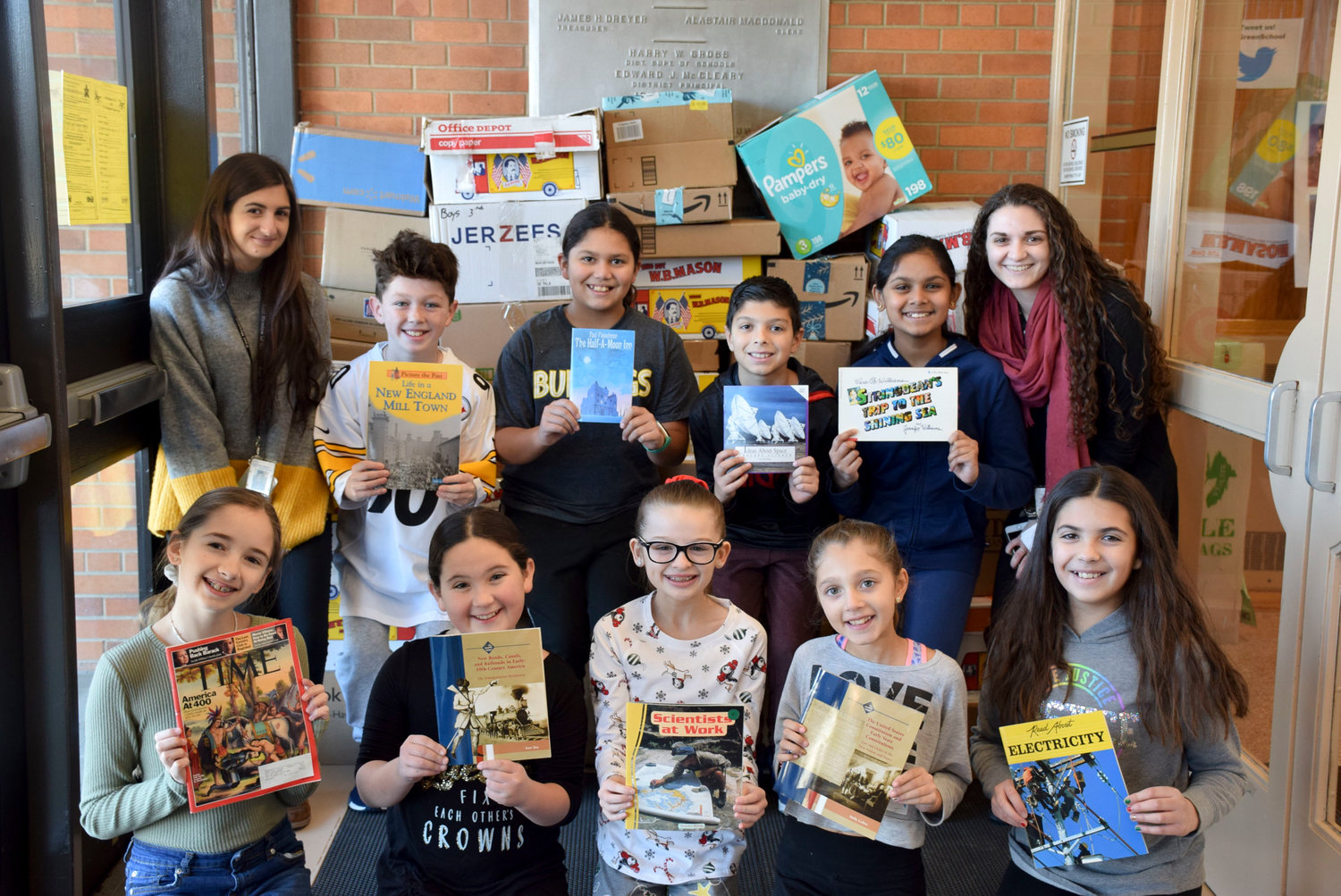 The K-Kids service organization board members, pictured with K-Kids advisers Christina Chrish (left) and Jacqueline Langro, collected 19 boxes of books to be donated to the Book Fairies for children in the community.