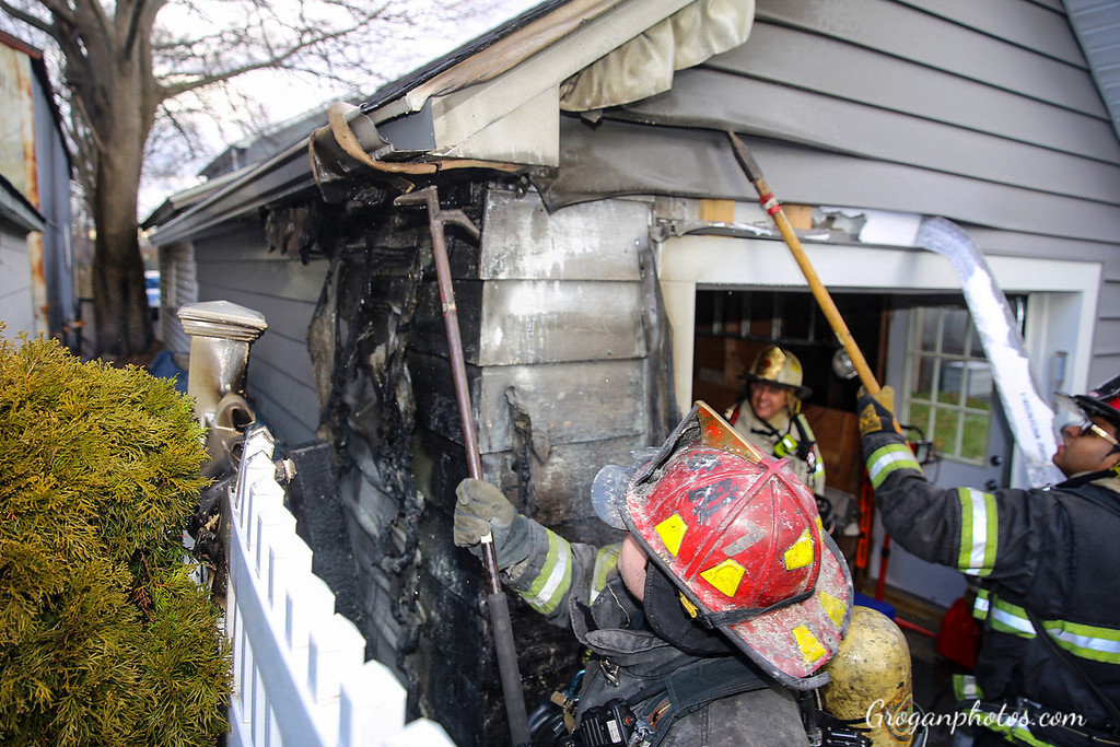 Lynbrook firefighters pulled down the siding on the detached garage on Wyoming Avenue after a fire on Sunday.