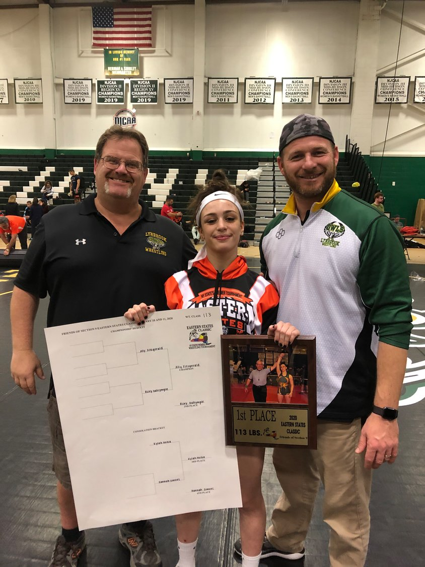 Lynbrook High School junior Ally Fitzgerald, 16, earned another historic victory when she took home the 113-pound championship at the Eastern States Classic's first all-girls wrestling tournament earlier this month. With her were coach Rich Renz, left, and assistant coach Ed Parenteau.