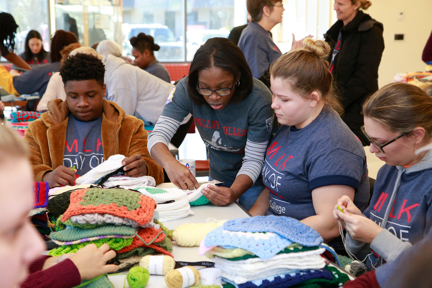 Molloy staffer Donna Headley showed Molloy student Courtney Copf how to stitch crocheted squares together to make blankets.
