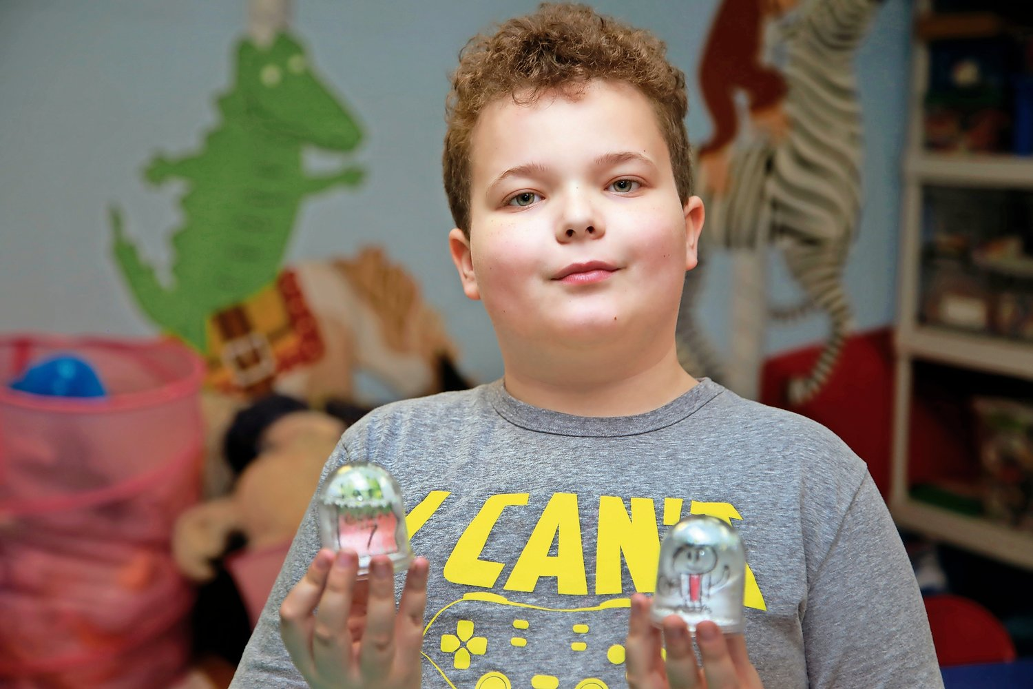 Polk School fifth-grader Justin Grassia with two snow globes he made at the Franklin Square Public Library on Jan. 29.