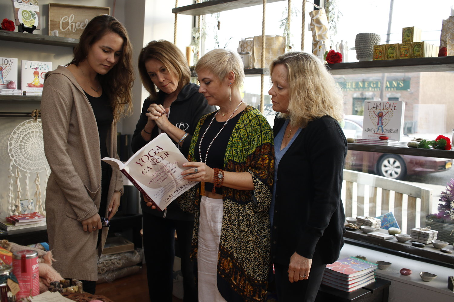 Yoga instructor Samantha Wondsel, far left, student Cathy Duffy, studio owner Laura Shockley and student Rosemary Gibson, conferred over a book written by Tari Prinster, about methods of training people with cancer.