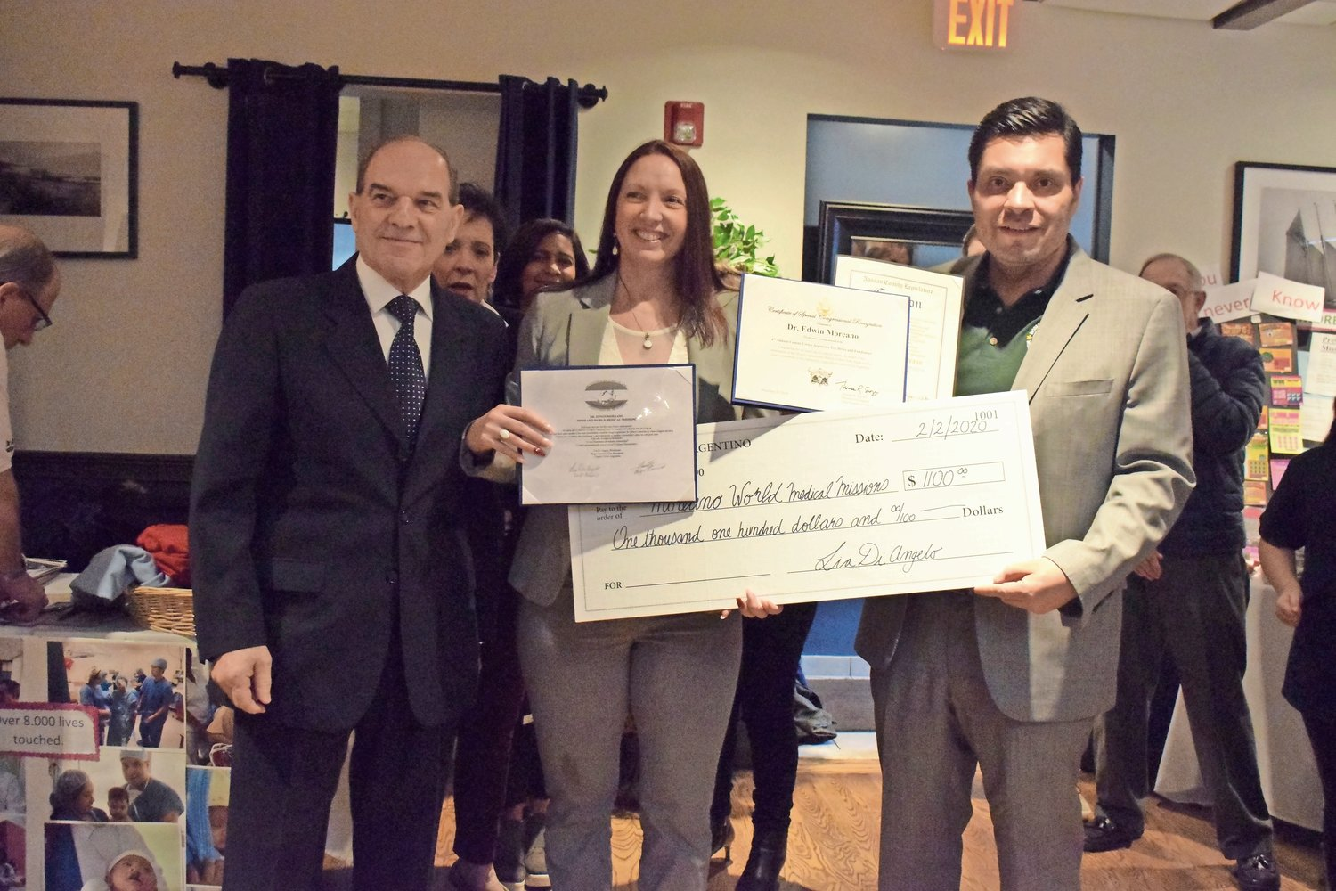 Comite Civico Argentino Vice President Hugo Amorini, far left, and President Lia Di Angelo presented a check to Dr. Edwin Moreano for his mission work in Latin America.