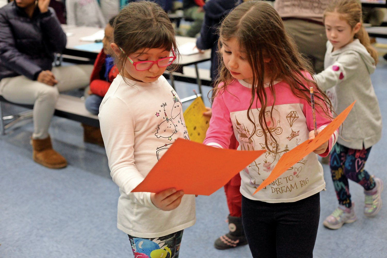 Twins Michaela, left, and Mary Ann Scarnati, 7, compared their scavenger hunt lists before searching for the next item at Bayville Primary's Family Night on Jan. 15.